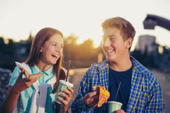 Two cheerful teenagers, girl and boy, eating pizza Stock Photos