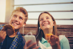 Two cheerful teenagers, girl and boy, eating pizza Royalty Free Stock Photo