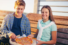 Two cheerful teenagers, girl and boy, eating pizza outdoor Royalty Free Stock Images