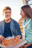 Two cheerful teenagers, girl and boy, eating pizza outdoor Stock Image