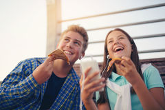 Two cheerful teenagers, girl and boy, eating pizza Stock Images