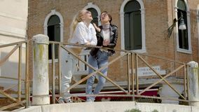 Two cheerful townswomen are chatting standing on embankment of italian city in spring sunny day. Two cheerful townswomen are chatting joyfully and laughing stock footage