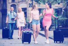 Two cheerful traveling girls walking in city stock image