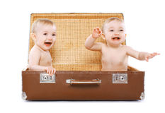 Two cheerful twins sitting in a suitcase Stock Images