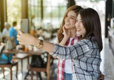Two cheerful woman taking selfie on smartphone royalty free stock photo