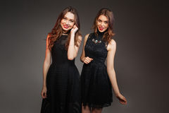 Two cheerful women in black dresses going to party together. Two cheerful beautiful women in black dresses going to party together over grey background Stock Photo