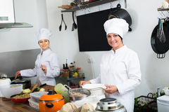 Two cheerful women chefs cooking food at kitchen Royalty Free Stock Photography
