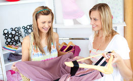 Two cheerful women choosing clothes together Royalty Free Stock Image