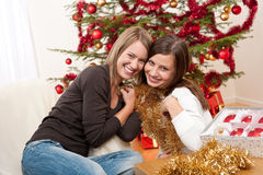 Two cheerful women with Christmas chains and balls Stock Photography