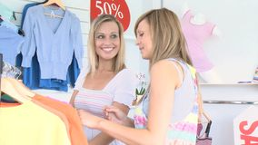 Two cheerful  women are doing shopping. Two cheerful women are doing shopping in a clothes store stock video footage