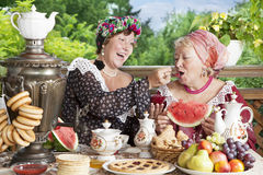 Two cheerful women drinking tea  with bagels and jam outdoors Royalty Free Stock Photo