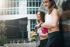 Two cheerful women runners stand leaning against trailer, rest after training, drink water, looking on pulsometer. stock photos