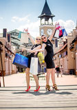 Two cheerful women with shopping bags posing on street Stock Photos