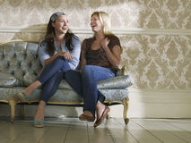 Two Cheerful Women Sitting On Sofa Stock Photo