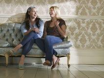 Two Cheerful Women Sitting On Sofa stock photo