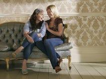 Two Cheerful Women Sitting On Sofa royalty free stock photos