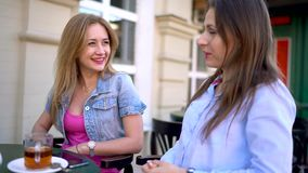 Two cheerful women talk in a cafe stock footage