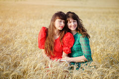 Two cheerful women in a wheat field at sunset in a blue and red long air dress. Stock Photography