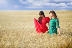 Two cheerful women in a wheat field at sunset in a blue and red long air dress. Royalty Free Stock Photos