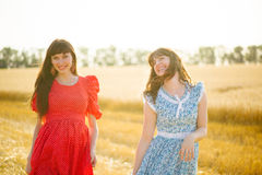 Two cheerful women in a wheat field at sunset in a blue and red long air dress. Royalty Free Stock Images