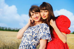 Two cheerful women in a wheat field at sunset in a blue and red long air dress. Royalty Free Stock Image