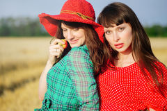 Two cheerful women in a wheat field at sunset in a blue and red long air dress. Royalty Free Stock Photo