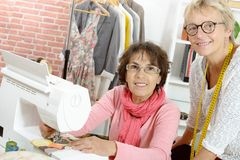 Two cheerful  women working together in their Stock Photo