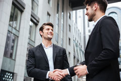 Two cheerful young businessmen shaking hands Royalty Free Stock Photography