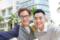 Two cheerful young businessmen standing and taking selfie in off royalty free stock photo