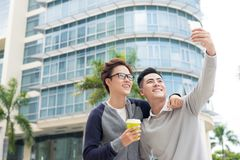 Two cheerful young businessmen standing and taking selfie in off stock image
