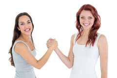 Two cheerful young female friends arm wrestling Royalty Free Stock Photos