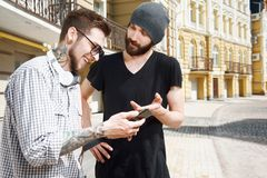 Two cheerful young friends are talking in city Stock Image