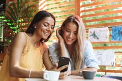 Two cheerful young girlfriends sitting at the cafe indoors. Drinking coffee, looking at mobile phone royalty free stock photography