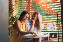 Two cheerful young girlfriends sitting at the cafe indoors. Drinking coffee, reading magazine royalty free stock photo