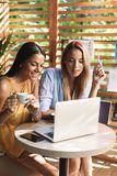 Two cheerful young girlfriends sitting at the cafe indoors. Drinking coffee, using laptop computer royalty free stock photos
