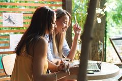 Two cheerful young girlfriends sitting at the cafe indoors. Drinking coffee, using laptop computer royalty free stock images