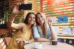 Two cheerful young girlfriends sitting at the cafe indoors. Drinking coffee, taking a selfie royalty free stock photo