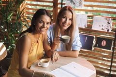Two cheerful young girlfriends sitting at the cafe indoors. Drinking coffee, reading magazine royalty free stock image