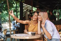 Two cheerful young girlfriends sitting at the cafe table. Indoors, taking a selfie royalty free stock images