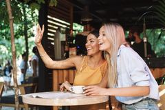 Two cheerful young girlfriends sitting at the cafe table. Indoors, waving hand royalty free stock photo