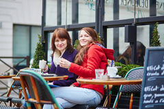 Two cheerful young girls in a Parisian street cafe Stock Photos