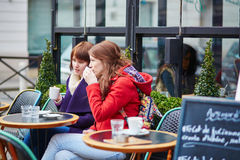 Two cheerful young girls in a Parisian street cafe Royalty Free Stock Image