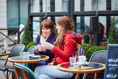 Two cheerful young girls in a Parisian street cafe Royalty Free Stock Photography