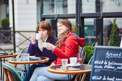 Two cheerful young girls in a Parisian street cafe Stock Image