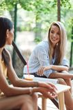 Two cheerful young girls sitting at the cafe outdoors. Drinking smoothies royalty free stock photos