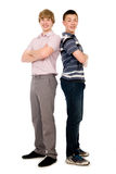 Two cheerful young students standing back to back. Stock Photos