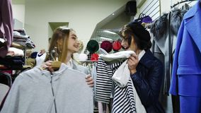 Two cheerful young woman choosen a clothes and very happy. Go to try on the clothes stock footage