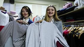 Two cheerful young woman choosen a clothes and very happy. Go to try on the clothes. Girls have some fun in the store stock video