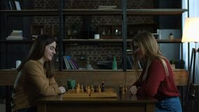 Two cheerful young women playing chess at home stock video footage