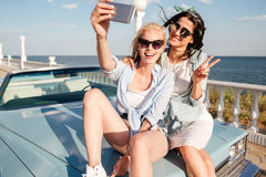 Two cheerful young women sitting on car and taking selfie royalty free stock photo